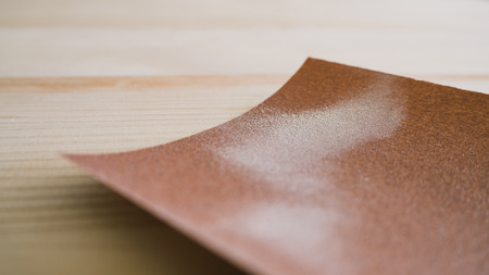 Cleaning stain on wooden table with sandpaper.