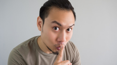telling: Asian man is telling a secret. Do not tell anyone.
