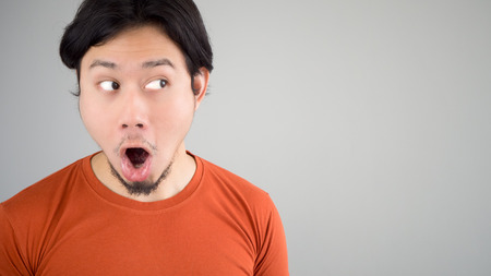 red tshirt: Unbelievable face of Asian man in red t-shirt. Stock Photo