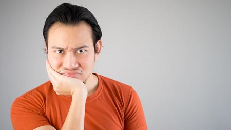 unsatisfied: Asian man is feeling unsatisfied.