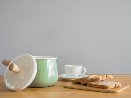 Wooden and stainless kitchenware on wooden table. Pastel utensil boiler with wooden handle.