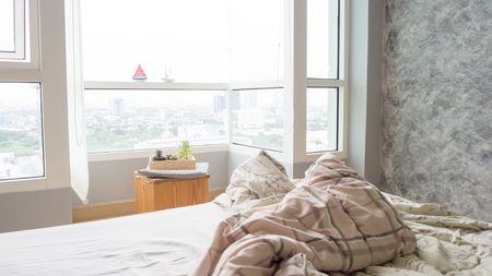 bed sheet: Unmade bed with crumpled bed sheet, a blanket and pillows after waking up in the morning. Stock Photo