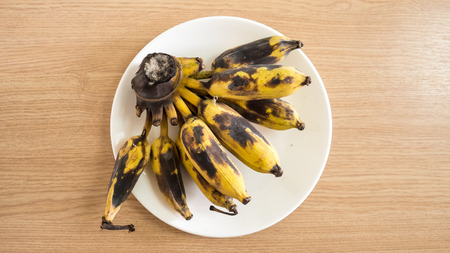 overripe: Top view of bunch of overripe banana on white dish.