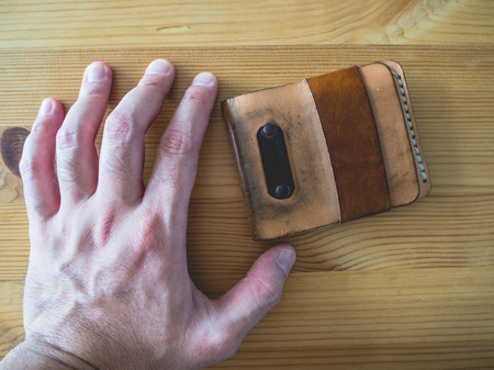 cash cow: Grunged and dirty leather wallet on wooden table. Hand grab leather wallet. Stock Photo