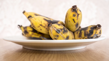 overripe: Bunch of overripe banana on white dish. Stock Photo