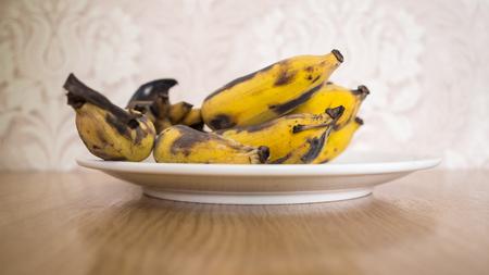 Bunch of overripe banana on white dish. Stock Photo