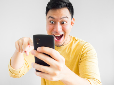 Asian man is playing mobile game.