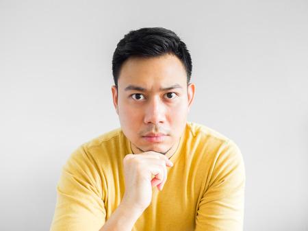 Aziatische man in yellown overhemd serieus te denken, Aziatische man gekruist arm. Stockfoto