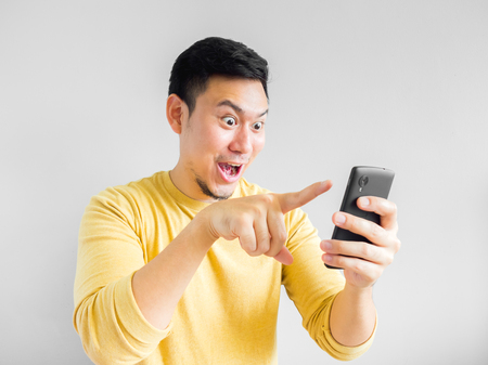 Asian man is playing mobile game. 스톡 콘텐츠