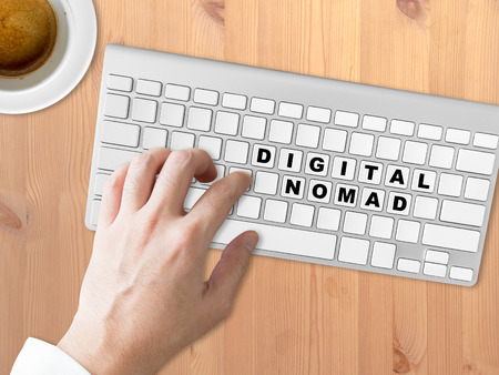 nomad: Concept of Digital Nomad words on the button of the keyboard. Stock Photo