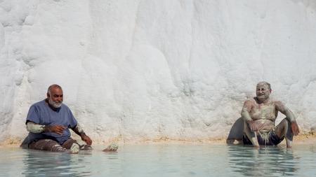 pamukkale: Pamukkale, Denizli, Turkey - September 14, 2016: Local tourists bathing in the natural pool of Pamukkale.