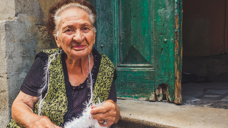12 step: Balat, Istanbul, Turkey - September 12, 2016: Happy old woman knitting in front of her door step.