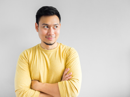 Asian man in yellown shirt seriously thinking, Asian man crossed arm.