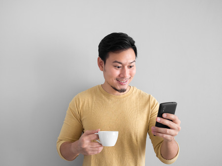 Asian man having a cup of coffee and using smartphone. Archivio Fotografico