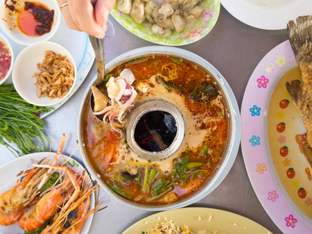 favorite soup: Top view of traditional Thai spicy food. Fried rice. Tom yum koong soup. Grilled shrimps. Fresh oysters.