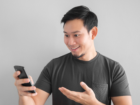 Asian man is using smartphone. Black t-shirt mourn for Thai king.