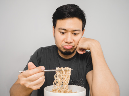Poor Asian man feel boring with the same old instant noodle.