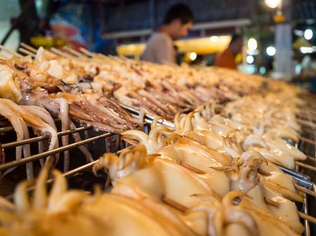 squids: Grilled squids on stick Thai streetfood in Bangkok. Stock Photo