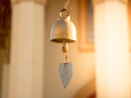 Thai temple smalls bells with golden leaf in morning light.