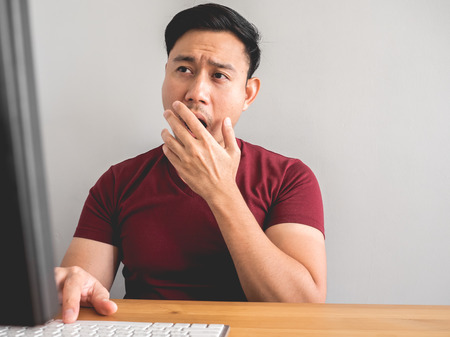 Asian man feel sleepy and bored with his office work.