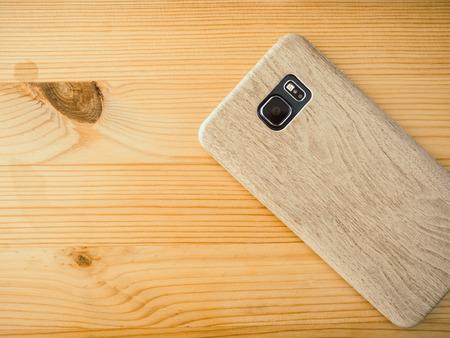 Smartphone in screen wooden case on work desk.