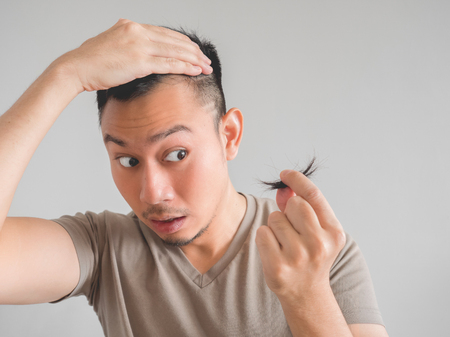 clipper: Asian man cut his own hair with clipper and scissor. Stock Photo