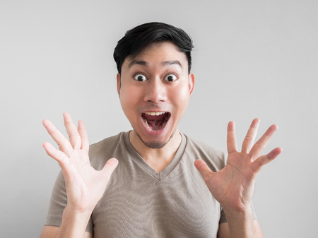 Asian man feels shock and surprise with overly face expression.