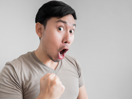 overly: Asian man feels shock and surprise with overly face expression.
