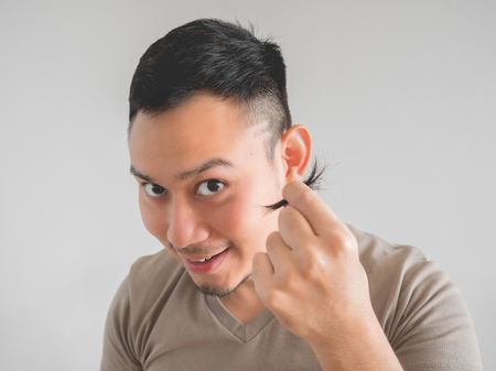Asian man cut his own hair with clipper and scissor. Stock Photo