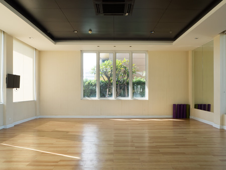 Empty fitness room with yoga mat television and garden view windows.