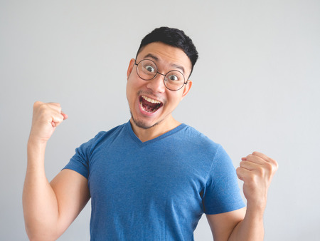 Funny surprised and overjoyed face of Asian man in blue t-shirt and eyeglasses.
