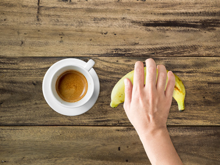 grab: Cup of hot coffee and a hand grab on banana. Set of diet meal. Stock Photo