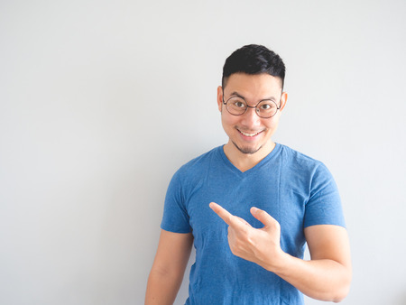 dictatorial: Happy Asian man is presenting something with hand point out to empty space. Stock Photo