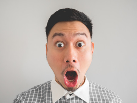 Close up of straight face of surprised and shocked Asian man with light beard.
