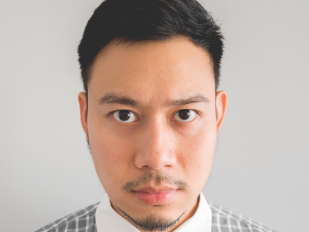 vietnamese ethnicity: Close up of straight face of serious Asian man with light beard. Stock Photo