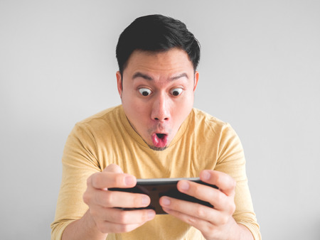 Shocked Asian man plays mobile game in his smartphone.