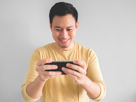 Happy Asian man plays mobile game on smartphone.
