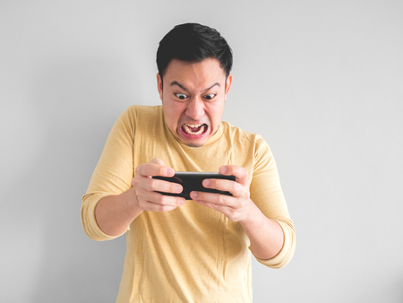 Angry Asian man plays mobile game on his smartphone. Stockfoto