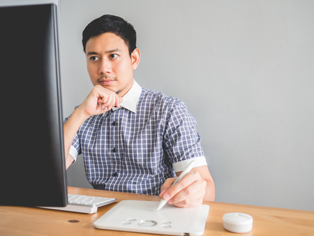 Thoughful Asian ceative freelance man doing his job. Stock Photo