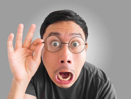 Faccia divertente sconvolta e sorpresa dell'uomo asiatico con gli occhiali e la barba. Archivio Fotografico - 79127383