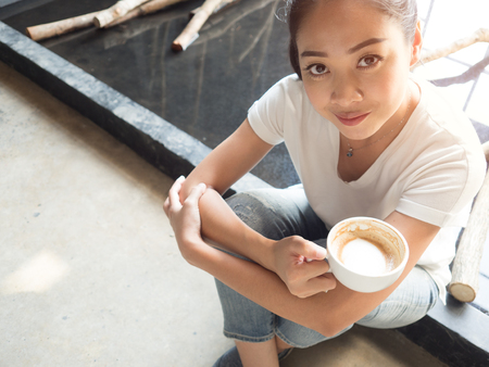 Asian woman takes a coffee break after hard work. Stock Photo
