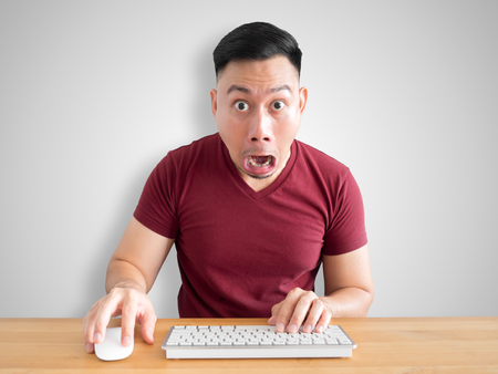 Shock and wow face of Asian man sit on his desk working in the office.