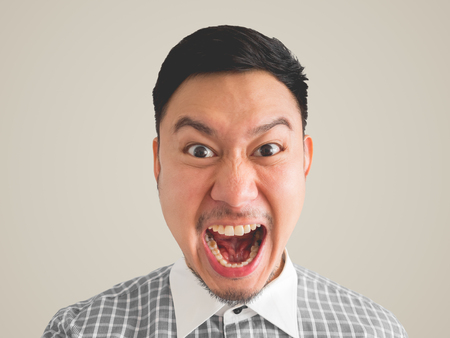 japanese people: Close up of straight face of mad Asian man with light beard. isolated on cream colour background.