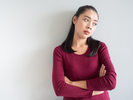Unhappy and annoyed face of Asian woman standing.