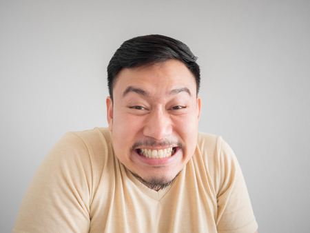 Headshot of funny guilty face of Asian man with beard and mustache.