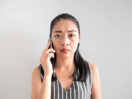 Unhappy and angry  Asian woman talking phone call on smartphone. Stock Photo