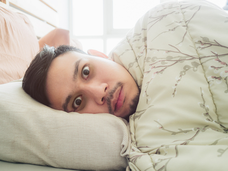 Asian man can not sleep in the morning light with sleepless black eyes.