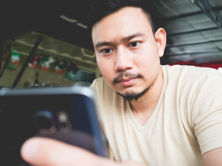 phon: Asian man using mobile phone in an outdoor cafe.