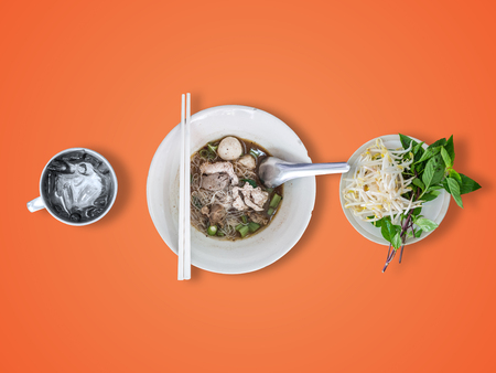 Top view of Thai rice noodles thicken soup with vegetables set and ice water cup.