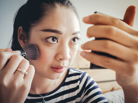Asian woman putting on make up in bedroom.